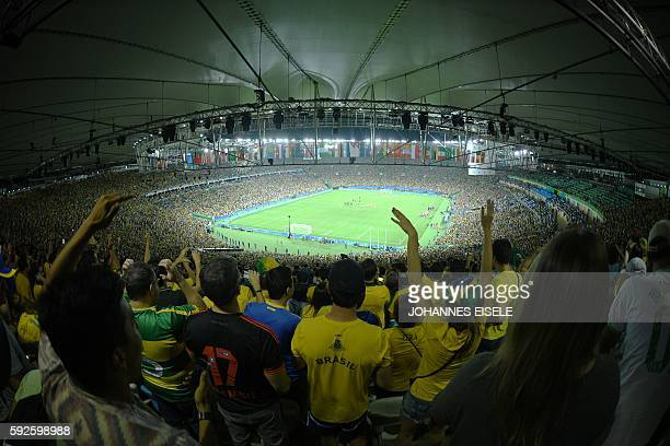 TOPSHOT Brazil's supporters celbrate after winning the penalty shootout of the Rio 2016 Olympic Games men's football gold medal match between Brazil...