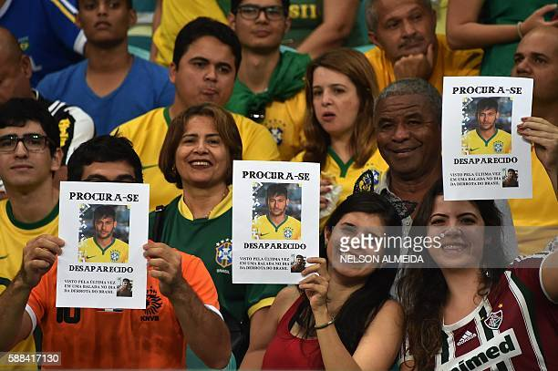 TOPSHOT Brazil's supporters hold photos of Brazilian footballer Neymar reading 'Wanted Disappeared' as they cheer for their team during the Rio 2016...