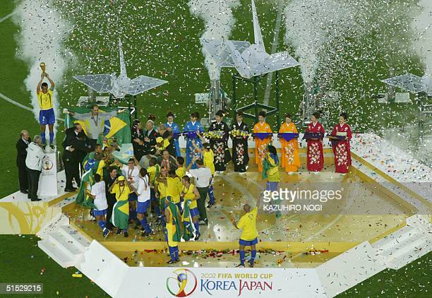 Brazil's team captain and defender Cafu hoists the World Cup trophy as teammaters celebrate during the award ceremony at the International Stadium...