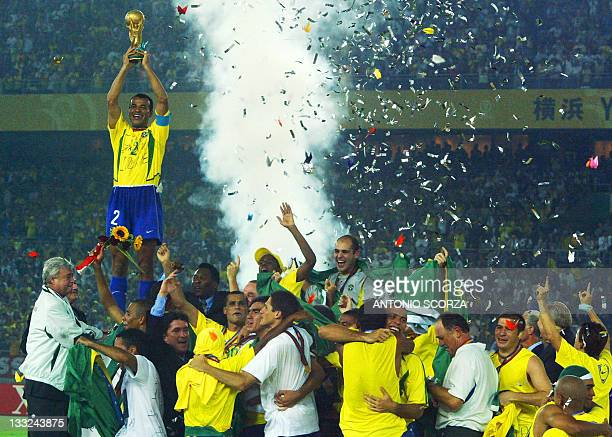 Brazil's team captain and defender Cafu hoists the World Cup trophy over the whole Brazilian team as confetti fall over the pitch during the award...