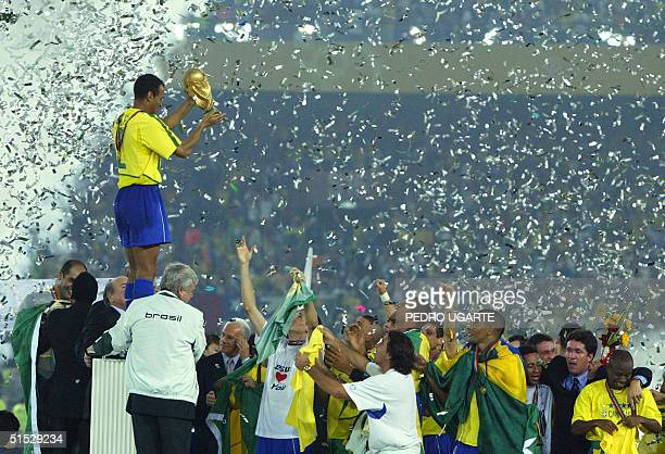 Brazil's team captain and defender Cafu hoists the World Cup trophy over his teammates celebrating Brazil's 20 victory over Germany in match 64 of...