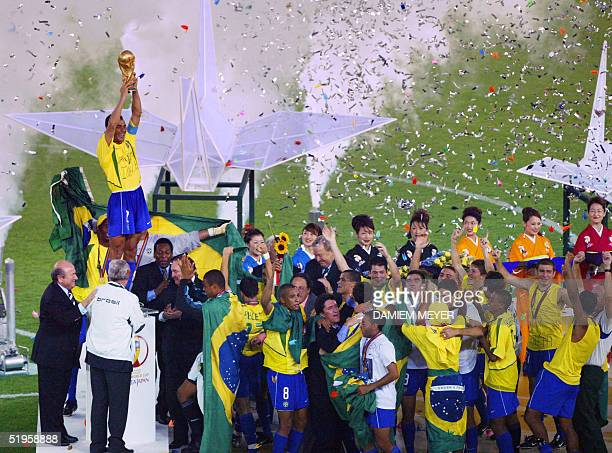 Brazil's team captain and defender Cafu hoists the World Cup trophy celebrating with his team following Brazil's 20 victory over Germany in match 64...