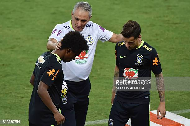 Brazil's team coach Tite speaks with players Willian and Philippe Coutinho after a training session at the Arena Dunas stadium in Natal Brazil on...