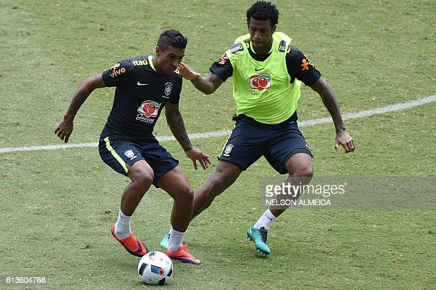 Brazil's team players Paulinho and Gil vies for the ball during a training session at the Arena Dunas stadium in Natal, Brazil on October 9, 2016...
