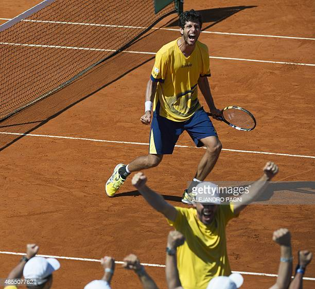 Brazil's tennis player Marcelo Melo celebrates along with team captain Joao Zwetsch after he and teammate Bruno Soares defeated Argentina's Carlos...