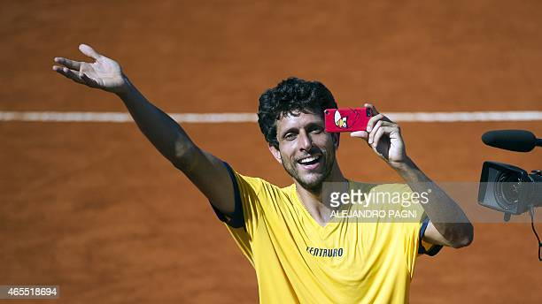 Brazil's tennis player Marcelo Melo takes a picture with a mobile phone after winning to Argentina's Carlos Berlocq and Diego Schwartzman with...