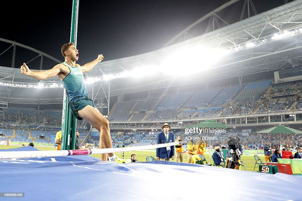 Brazil's Thiago Braz Da Silva celebrates after breaking an Olympic record and winning the gold medal in the Men's Pole Vault during the athletics competition at the Rio 2016 Olympic Games at the Olympic Stadium in Rio de Janeiro on August 15, 2016. / AFP / Adrian DENNIS