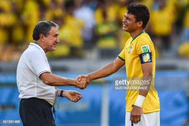 Brazil's Thiago Silva reacts with coach assistant Carlos Alberto Parreira at the end of the Round of 16 football match between Brazil and Chile at...