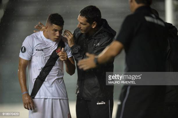 Brazil's Vasco da Gama player Paulinho receives medical attention after colliding with the goalkeeper of Bolivia's Jorge Wilstermann while he scored...