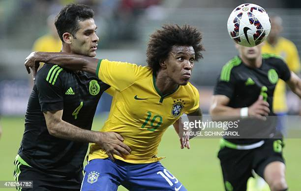 Brazil's Willian vies for the ball with Mexico's Rafael Marques during a friendly football match in preparation for the Copa America Chile 2015 at...