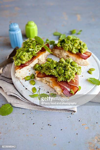 Bread and prosciutto sandwich with green broad beans