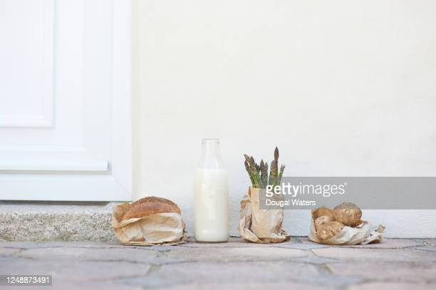 bread, bottle of oat milk, asparagus and potatoes outside front door of house. - community stock pictures, royalty-free photos & images