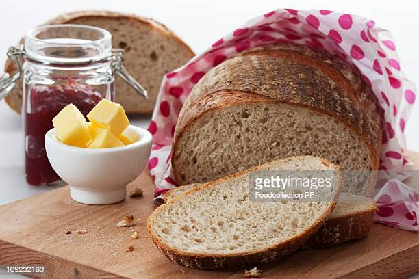 bread, butter and jam on chopping board - pane integrale foto e immagini stock