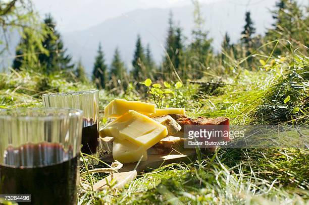 Bread, cheese and ham by glasses with red wine in meadow