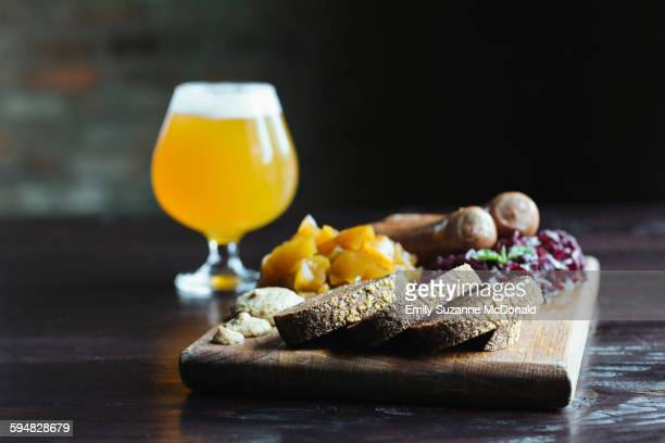 Bread, fruit and cheese on cutting board with beer