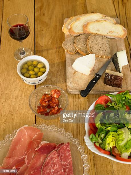 Bread, ham, salami, olives, cheese and salad on wooden table