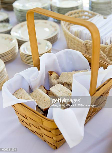 Bread in basket and stacks of plates on table