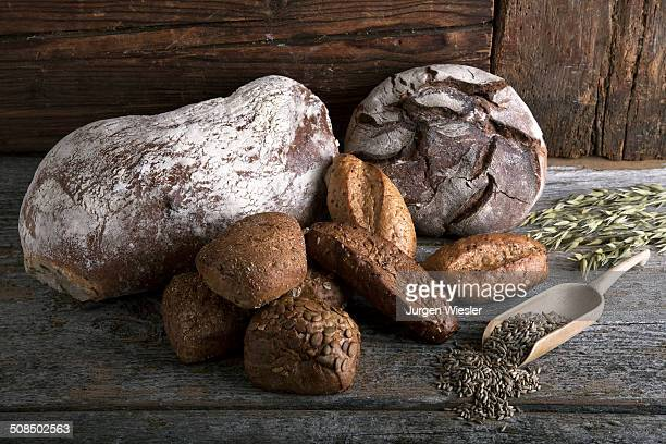 Bread loaves, rolls with rye grain and ears of corn on a rustic wooden surface