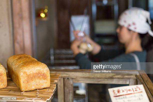 bread on the shelf of a bakery with baker behind