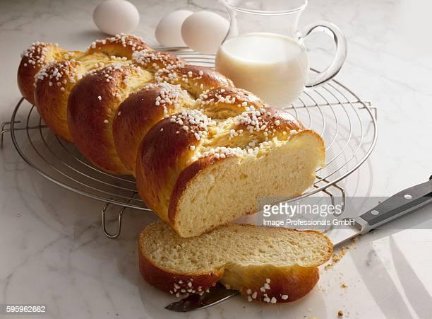 Bread plait with pearl sugar, milk jug & eggs in background