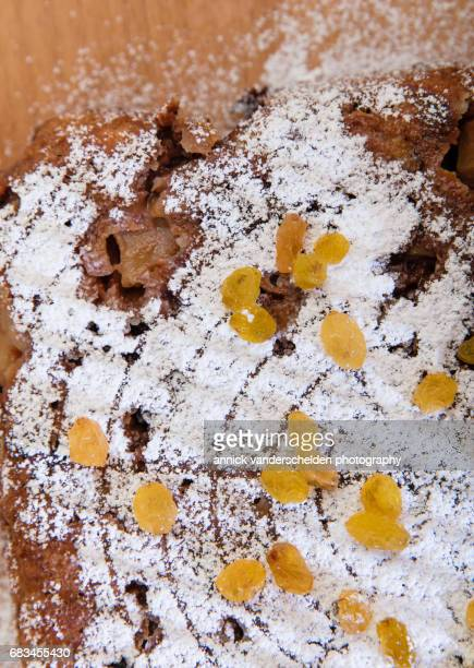 Bread pudding with icing sugar and raisins as garnish.