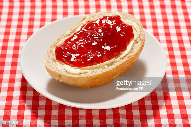 Bread roll with butter and strawberry jam