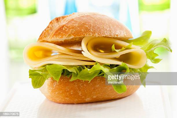 bread roll with emmentaler cheese on chopping board, close up - bun stock pictures, royalty-free photos & images