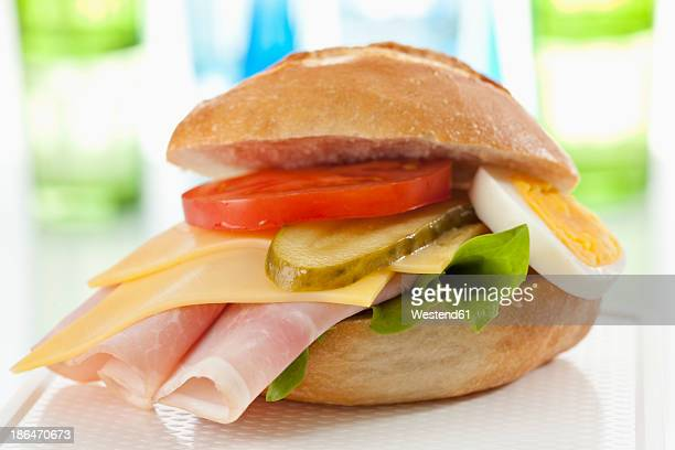 Bread roll with sliced processed cheese, ham, tomato, boiled egg and cucumber on chopping board, close up