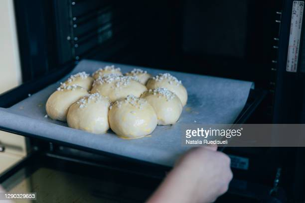 bread rolls arranged and being put into the baking oven. - brioche stock pictures, royalty-free photos & images