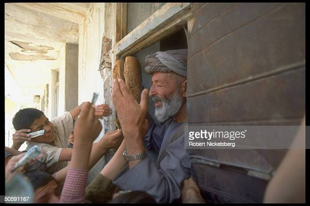 Bread seller being mobbed by paper moneythrusting customers in Kabul Afghanistan