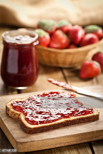 Bread slice spread with strawberry marmalade
