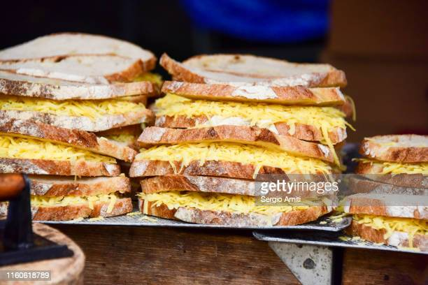 bread slices filled grated cheddar - sergio amiti stock pictures, royalty-free photos & images