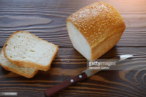 bread sprinkled with sesame on a wooden table, close-up. near piece of bread and knife. the concept of healthy organic food. farm products or homemade cakes. copy space. - gluten free bread stock pictures, royalty-free photos & images