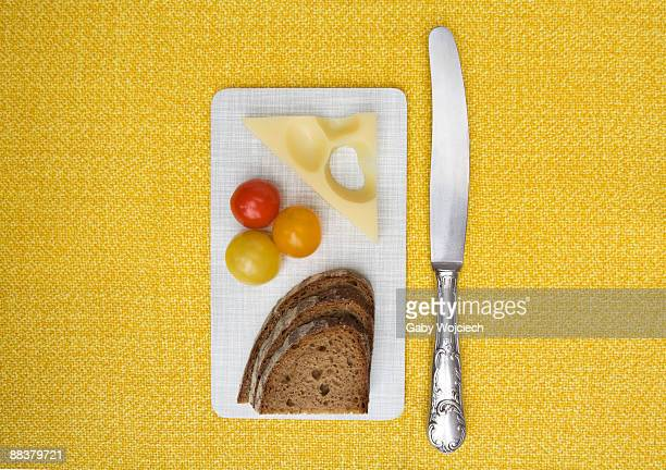 Bread, tomatoes and cheese on chopping board with knife, view from above, close-up