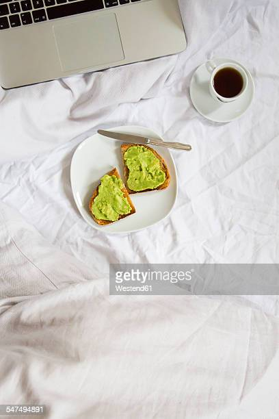 Bread with avocado cream and cup of coffee next to laptop