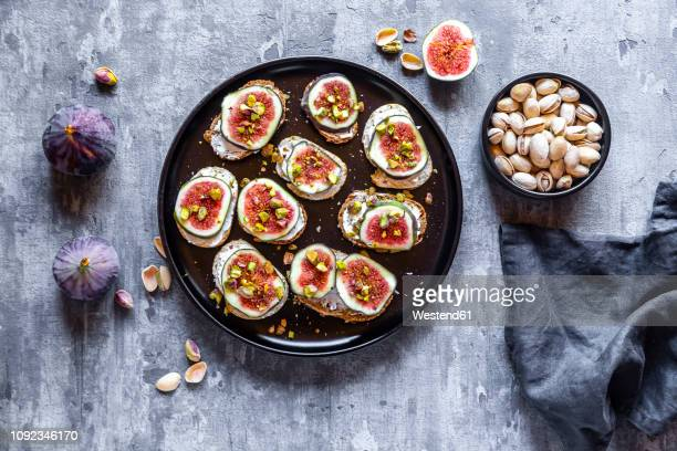 bread with goat cheese, figs and pistachio - fig stock pictures, royalty-free photos & images