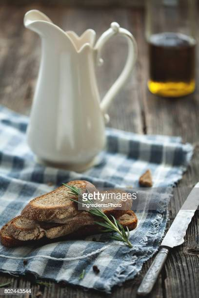 Bread with rosemary and jug of milk on the wooden table. Bottle of olive oil on background.