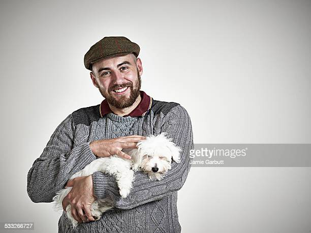Breaded male smiling whilst stroking a puppy