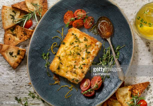 breaded, pan fried feta cheese (saganaki) with peppered honey and baked pita chips - feta cheese stock pictures, royalty-free photos & images