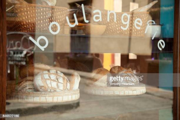 Breads are displayed ad seen through the window of a Mexican bakery