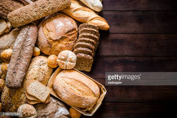 breads assortment with copy space on rustic wooden table - loaf of bread stock pictures, royalty-free photos & images