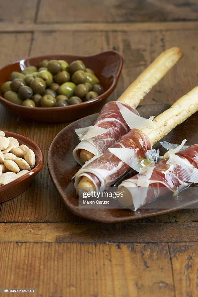 Breadsticks with prosciutto wrapped in plate, olives and almonds in dishes, close-up : Stockfoto
