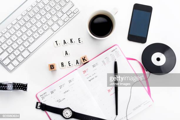 Break concept with open planner, keyboard, cup of coffee, phone lying on desk