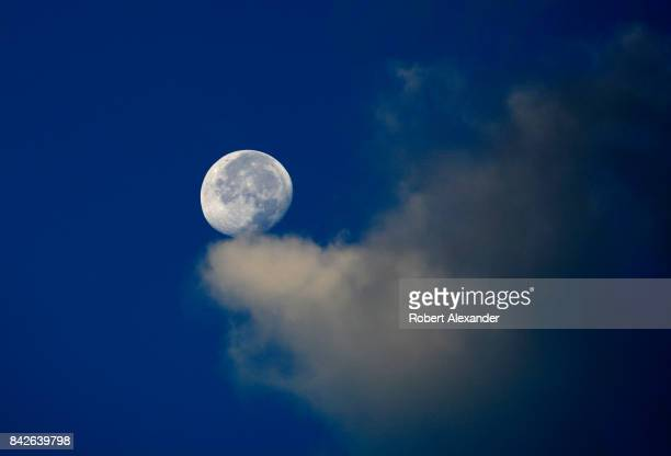 A break in the cumulus clouds allows a view of the moon from Santa Fe New Mexico