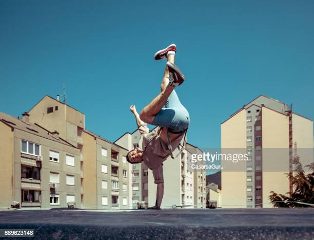 breakdancer dancing on a roof in a city - breakdancing stock photos and pictures