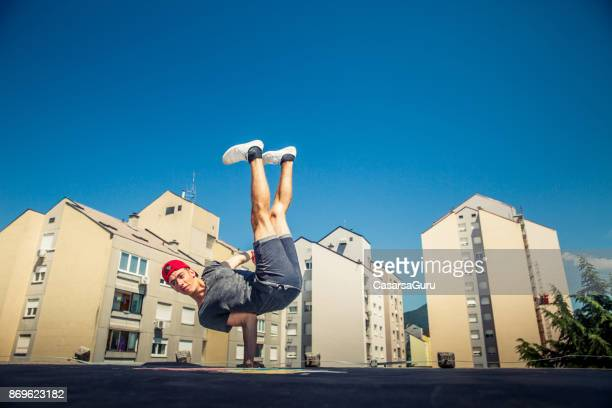 Breakdancer Dancing on a Roof in a City
