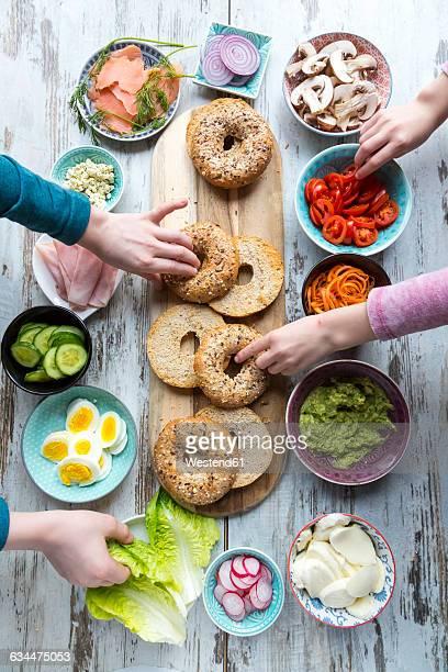 Breakfast, bagels, vegetables, salmon and ham, hands taking ingredients