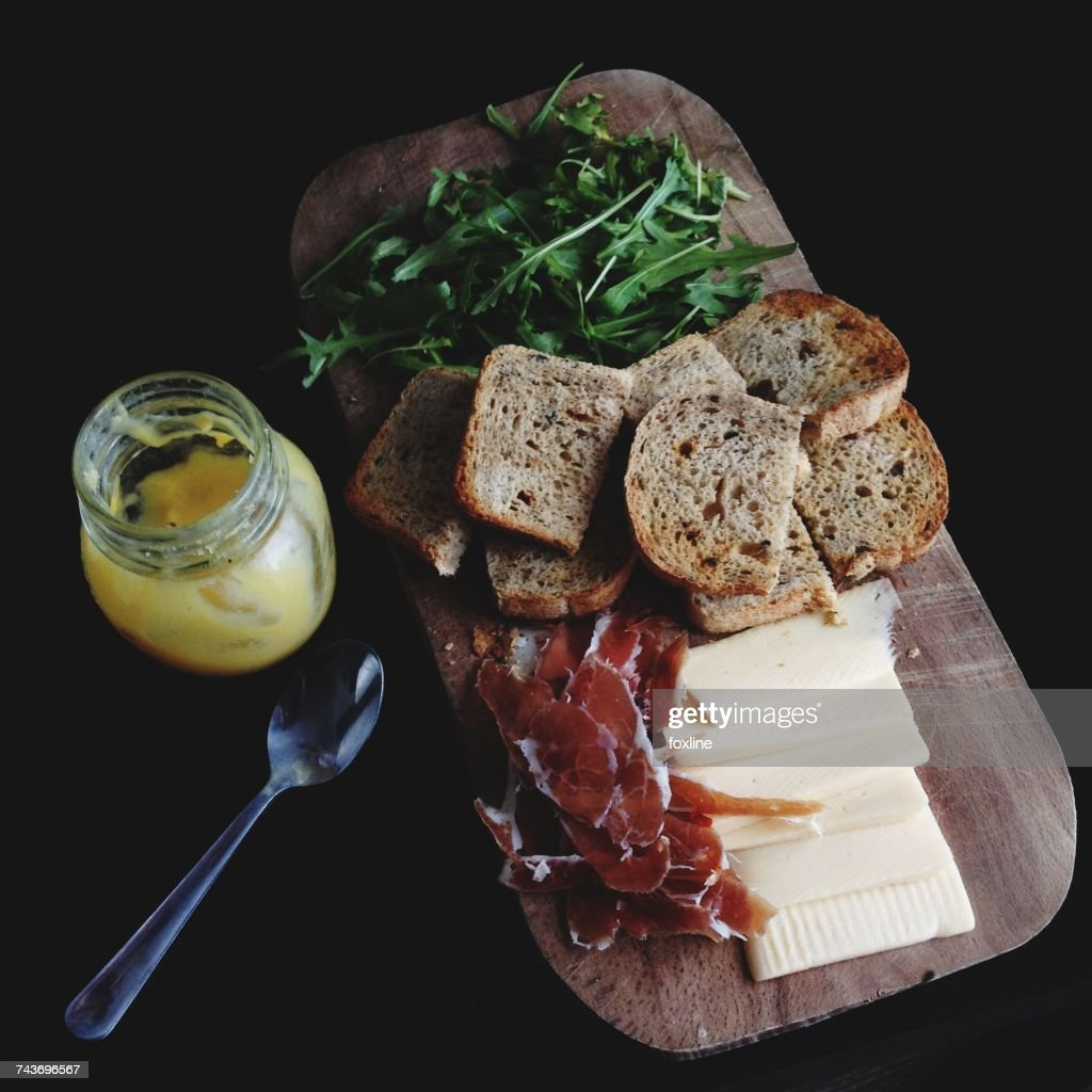 Breakfast board with bread, cheese, rocket leaves, prosciutto and a yogurt : Stock Photo