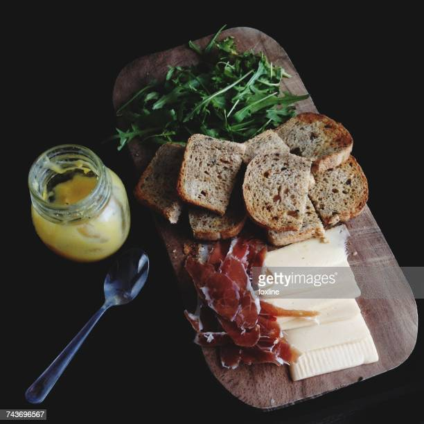Breakfast board with bread, cheese, rocket leaves, prosciutto and a yogurt