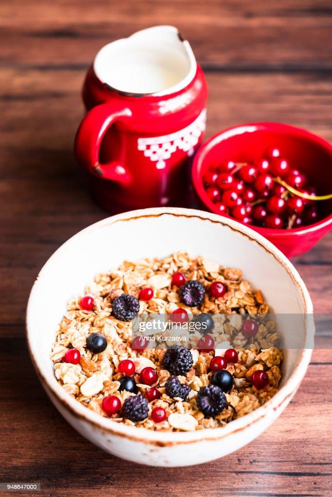 Breakfast bowl of homemade granola or muesli with toasted oat flakes, peanuts, black raspberry